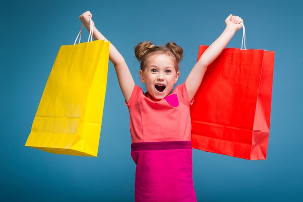 Little cute girl in pink dress holds purple paper bag