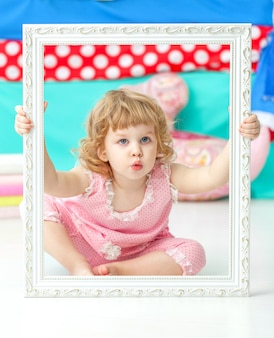 Little cute girl in a pink suit sitting on the floor and smiling over wooden white frame.