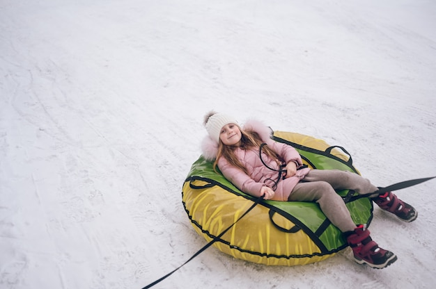 Little cute girl in pink warm outwear having fun rides inflatable snow tube in snowy white cold winter outdoors.