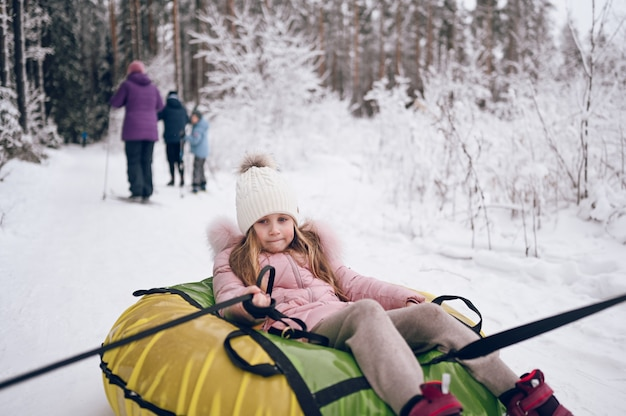 Little cute girl in pink warm outwear having fun rides inflatable snow tube in snowy white cold winter