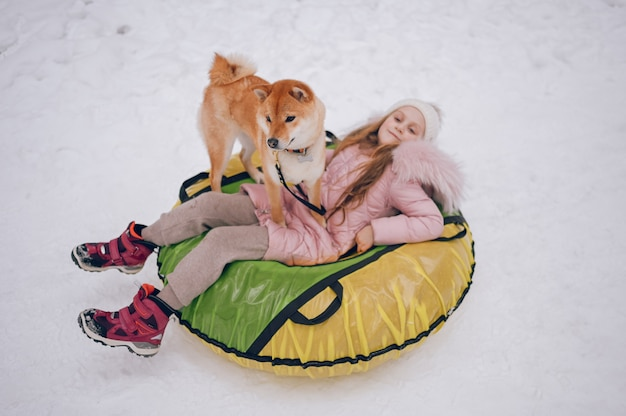 Little cute girl in pink warm outwear having fun with red shiba inu dog rides inflatable snow tube