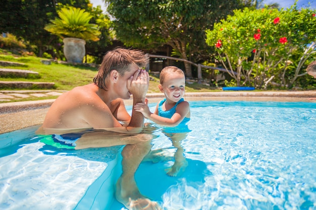 Little cute girl play with dad at the pool in tropical hotel