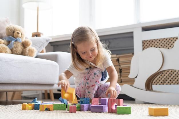 Маленькая милая девушка играет в игрушки блока в игровой у себя дома.
