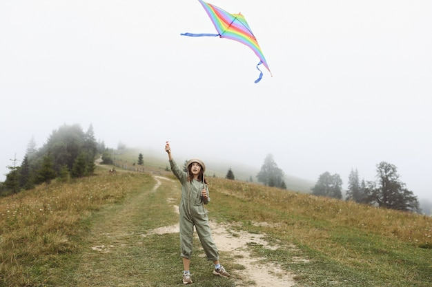 Little cute girl playing with colorful kite on foggy day in the mountains. happy child in green jumpsuit and cap is having fun outdoors