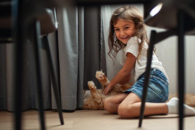 小さなかわいい女の子がメインクーンの猫と一緒に床で遊んでいます。ペットのコンセプト。