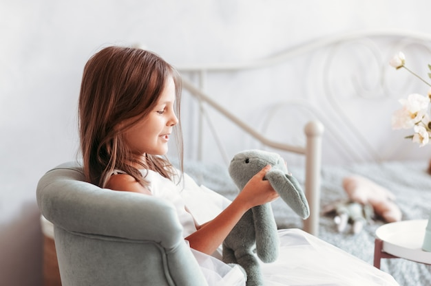 小さなかわいい女の子は、軽い子供の寝室でぬいぐるみで遊ぶ