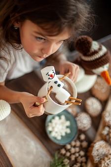 Маленькая милая девочка играет со связанными снеговиками, ест имбирные пряники и пьет какао с зефиром