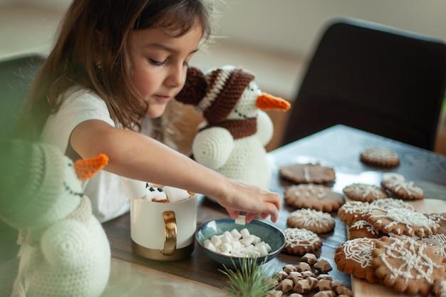 かわいい女の子は、雪だるまのニットで遊んだり、ジンジャーブレッドを食べたり、マシュマロと一緒にココアを飲んだりします。