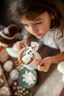 Little cute girl plays with knitted snowmen and eats gingerbread and drinks cocoa with marshmallows. stylish home kitchen and dining room. christmas preparation concept