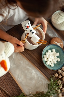 Little cute girl plays with knitted snowmen and eats gingerbread and drinks cocoa with marshmallows