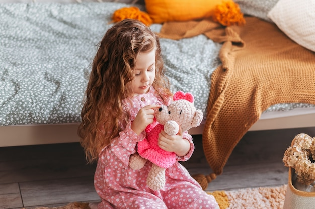 Маленькая милая девочка играет с мягким игрушечным мишкой на полу в детской спальне