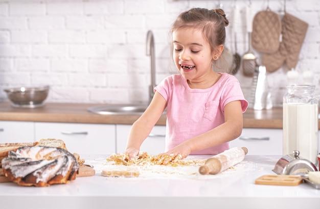 Маленькая милая девочка готовит тесто для домашней выпечки на фоне кухонного интерьера.