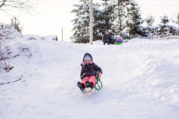 Little cute girl pulls a sled in warm winter day
