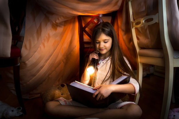Little cute girl reading book in selfmade house with flashlight