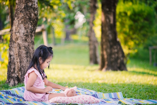 A little cute girl reading a book sitting under the tree