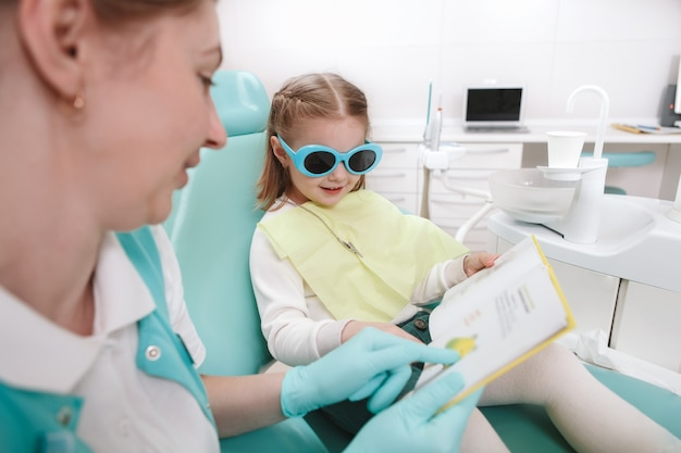 Little cute girl reading a book with her dentist