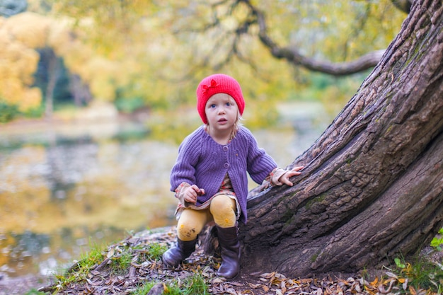 Little cute girl in red hat having fun at autumn park