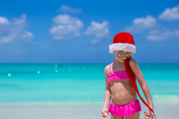 Little cute girl in red hat santa claus on the beach