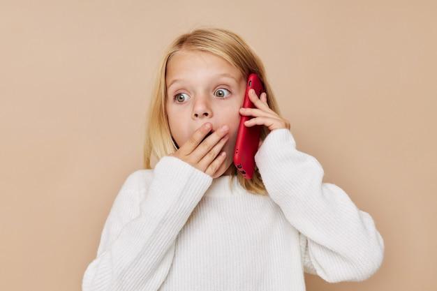 Маленькая милая девушка красный телефон в руке на бежевом фоне