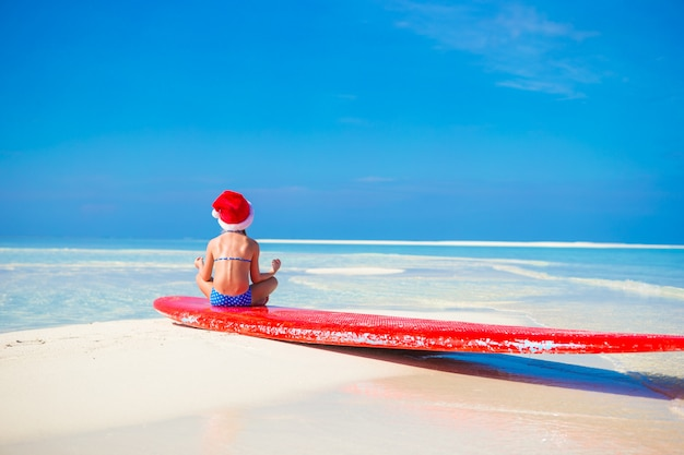 Little cute girl in santa hat on white beach during vacation in lotus position