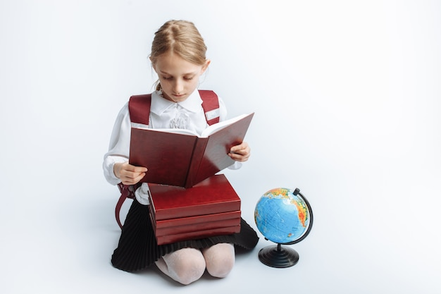 Little cute girl school girl sitting with books and a globe,reading a book