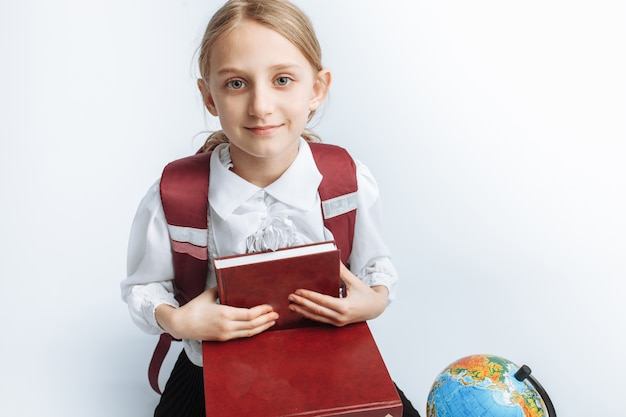 Little cute girl schoolgirl sitting with books and a globe, smiling and happy