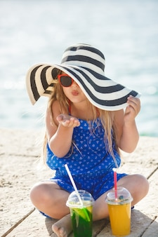 Little cute girl on the sea. girl in the hat in summer time. adorable child on the coastline.