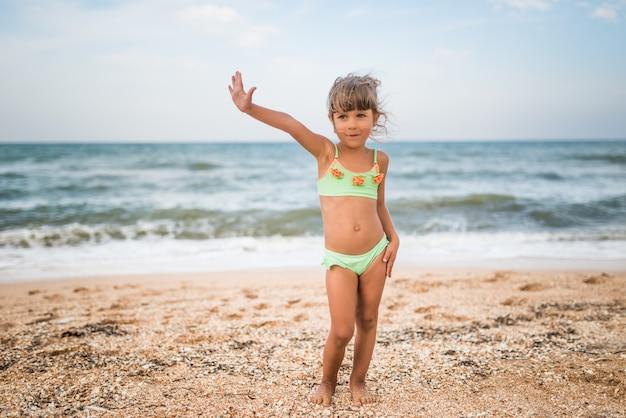 暖かい夏の日の週末に海で泳いでいる間、小さなかわいい女の子が親指を立てます。休暇中の幸せな子供たちの概念。コピースペース
