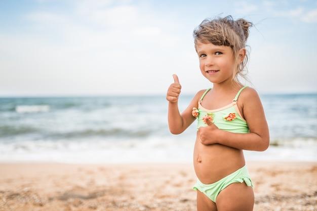 Маленькая милая девочка показывает палец вверх во время купания в море в выходные в теплый летний день