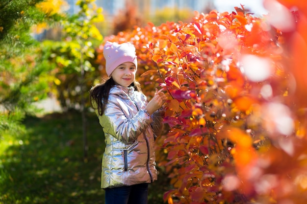 A little cute girl in a silver jacket walks in the autumn park on a sunny day
