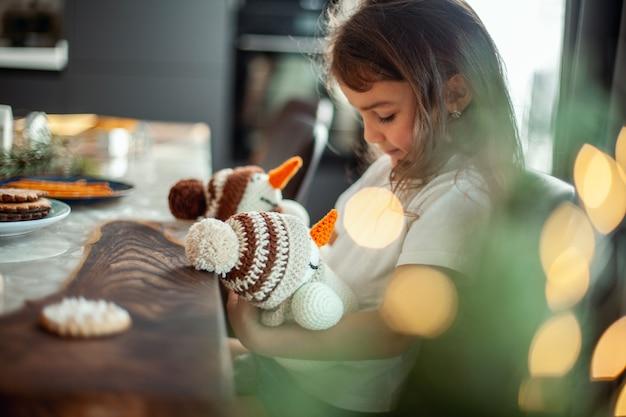 Маленькая милая девочка сидит за столом, наполненным рождественским декором, и он держит двух связанных снеговиков в ...