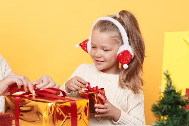 Маленькая милая девочка сидит за столом и держит рождественские подарки, изолированные над желтой студией.