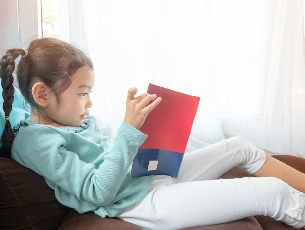 Little cute girl sitting on chair near the window and reading the book.