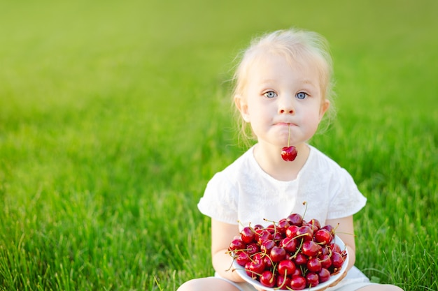 A little cute girl sitting on the grass with a plate of cherries on her knees and holding a berry in her teeth.