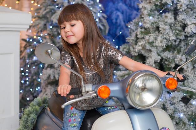 Маленькая милая девочка сидит на мотоцикле в рождество