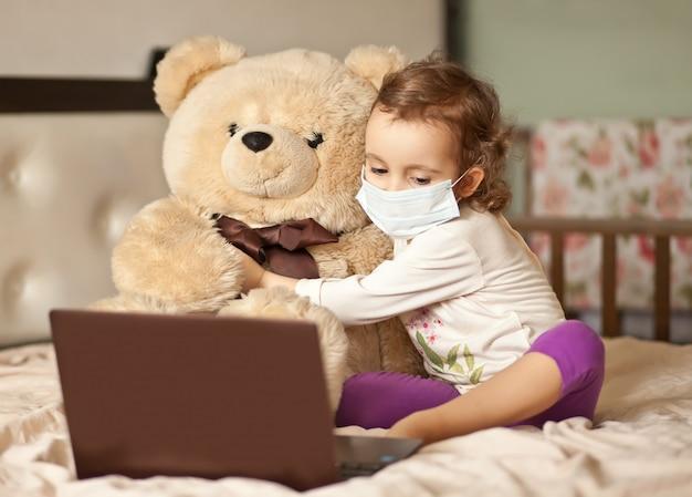 ベッドの上に座って、デジタルタブレットのラップトップノートを使用してかわいい女の子。友人や両親にオンラインで電話をかける。