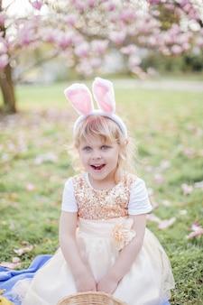 목련 근처 잔디에 앉아 귀여운 소녀. 부활절 토끼로 분장 한 소녀는 꽃과 달걀을 보유하고 있습니다. 봄.