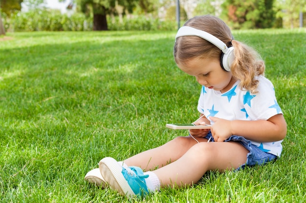 Little cute girl sitting in a park listening to music in white headphones