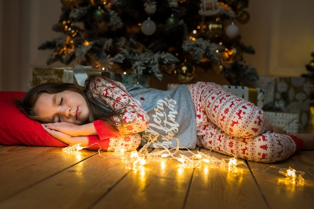 Little cute girl sleeping near a christmas tree waiting for santa happy child dreaming gifts