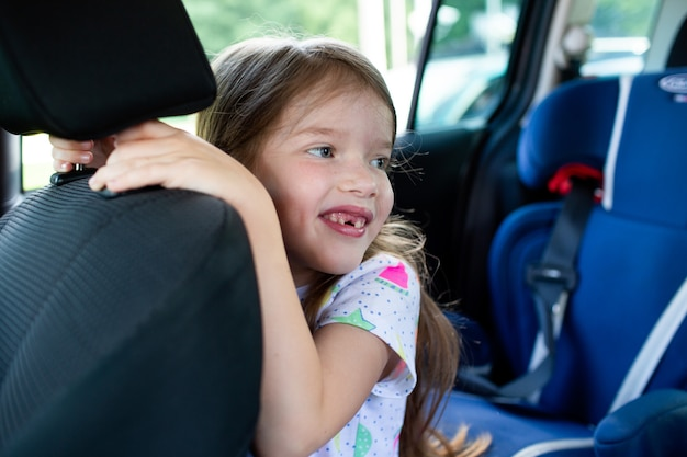 車の座席で笑っている小さなかわいい女の子