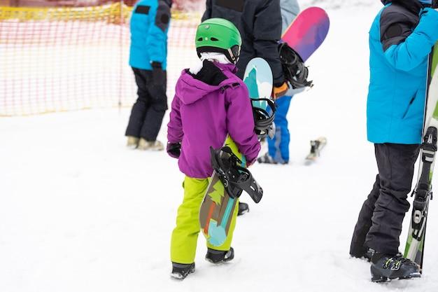 晴れた冬の日にスキーリゾートでスノーボードをするかわいい女の子。