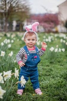 Маленькая милая девочка, стоящая на траве возле нарциссов