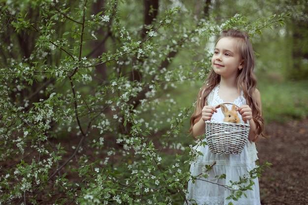 Маленькая милая девочка стоит в лесу и держит в руках корзину с кроликом.
