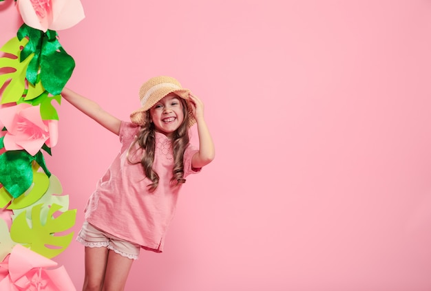 Little cute girl in summer hat on color wall