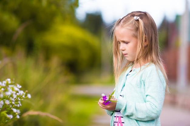 Little cute girl in summer park outdoors