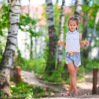 Little cute girl in summer park outdoors
