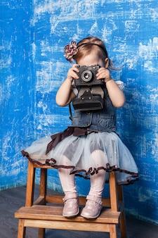 Маленькая милая девушка фотографирует