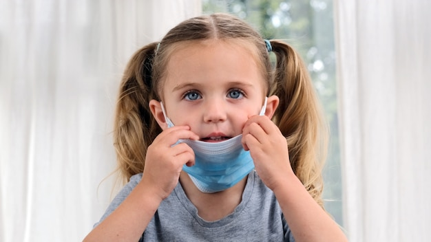 Little cute girl takes off her medical mask, smiles and puts it back on her face with ponytails. child is sick at home