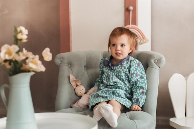 작은 귀여운 소녀 유아는 어린이 방에 의자에 앉아