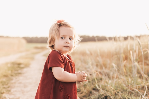 Маленькая милая девочка малыша, идущего через пшеничное поле